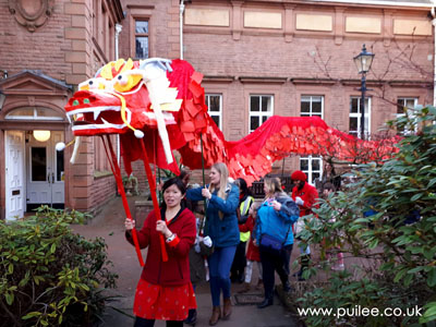 Artist Pui Lee leads the giant dragon through the parade