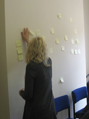 """Must Go To! (2012)"": handwritten post-it note installation on wall, dimensions variable"