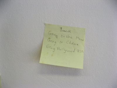 "Close-up of ""Must Go To! (2012)"": handwritten post-it note installation on wall, dimensions variable"